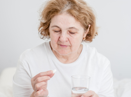 Senior woman holding pills and glass of water.
