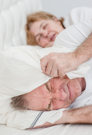 The elderly man covered his ears with a pillow so as not to hear the snoring of his wife. Stock Photo