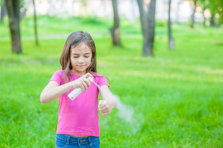 Girl spraying insect repellents on skin. Space for text. Banco de Imagens
