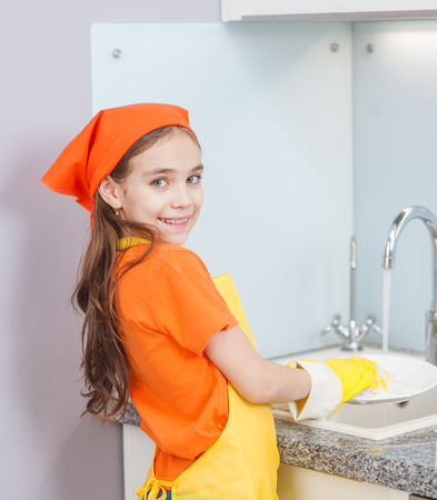 Happy little girl in an apron washes the dishes at the sink. Banque d'images