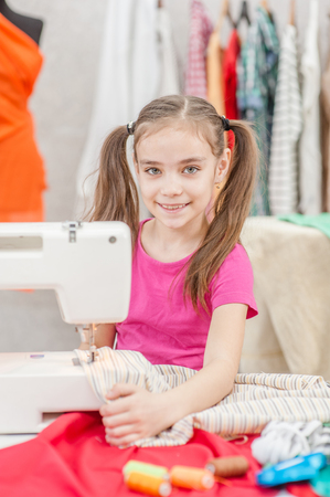 Smiling girl working on the sewing machine.