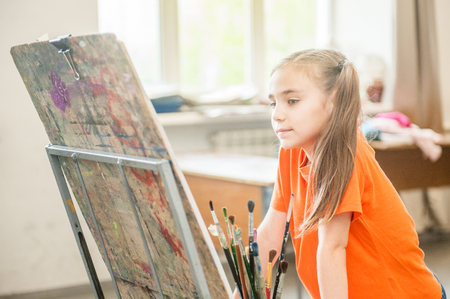 Little girl painter with easel at school. Talented kids. Stock Photo