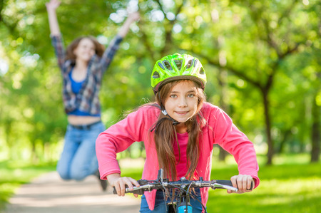 happy mother rejoices that her daughter learned to ride a bike.