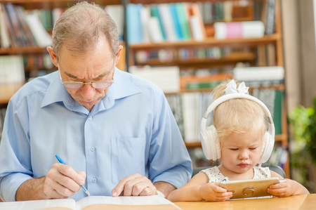 Baby girl uses the application on the phone, and an elderly man reads a book in the library.