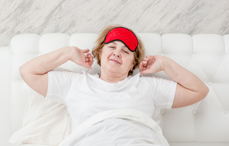 Senior woman sitting on her bed in the morning with arms raised in a stretch.
