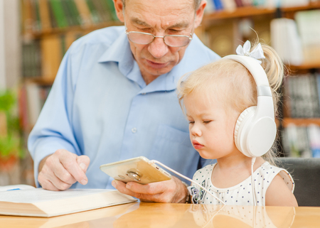 An elderly man with a little girl is using a smartphone in the library. Stockfoto