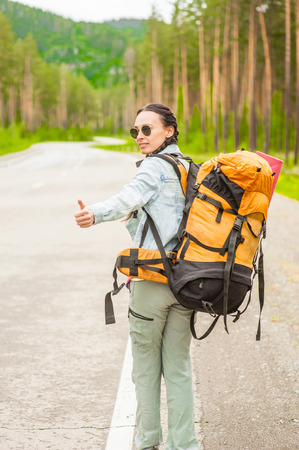 young woman with backpack hitchhiking along a road.