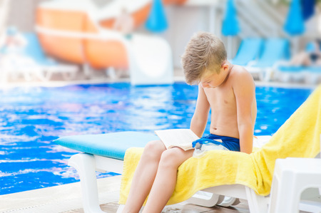 Little boy reading a book by the pool.  Relaxation resting vacations concept. Empty space for text. 版權商用圖片
