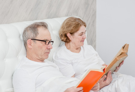 elderly couple reading a book on the bed. Stockfoto