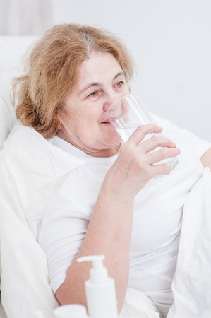 senior woman  drinks water before bedtime.