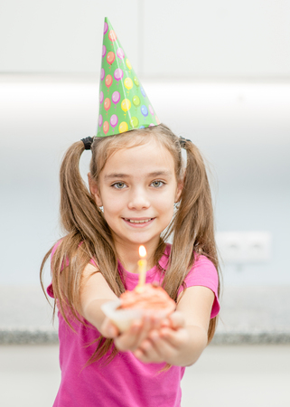 Smiling girl  in party hat gives birthday cupcake.