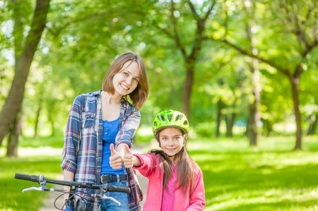 happy mom with her daughter on bicycles show thumbs up.