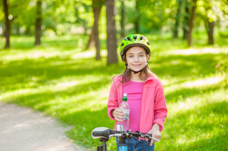 Smiling little girl with water by the bike. Space for text.