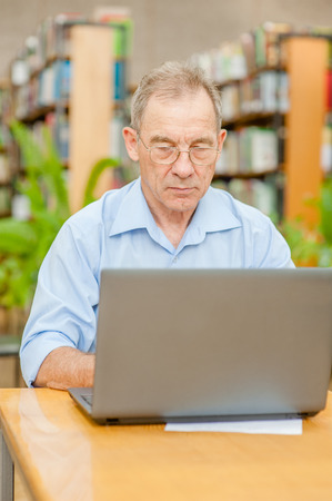 Senior man using laptop in librarySenior man using laptop in library. 免版税图像