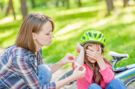 Mother puts a bandage on a wound to little girl, who fell off his bicycle. Focused on hands.