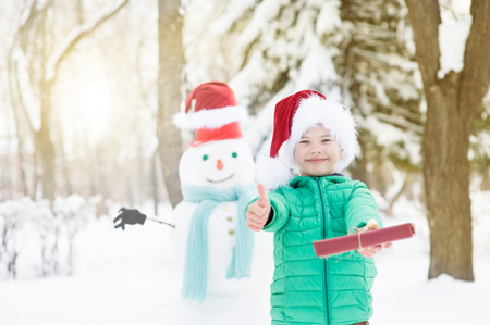 Smiling boy in red christmas hat with snowman on background holds gift box and showing thumbs up.
