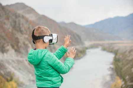 Little boy in virtual reality glasses stands on the background of the mountains.