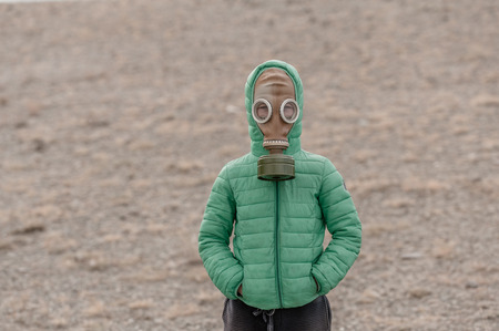 Child in a gas mask on a deserted field. Apocalypse postnuclear Doomsday scenario.