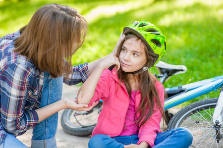 Mom puts a bandage on a wound to daughter, who fell off his bicycle.