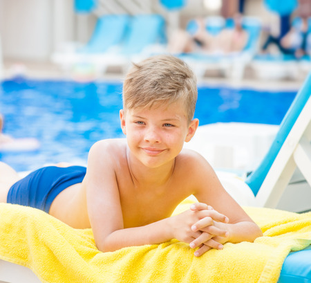 Little boy by the pool.  Relaxation resting vacations concept.