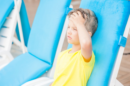 Little boy on the beach with a sunstroke touches his forehead, checking the temperature. Stock Photo