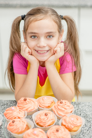 Smiling little girl with tray of a cupcakes.