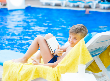 Little boy reading a book by the pool showing thumbs up.  Relaxation resting vacations concept. Empty space for text. Standard-Bild