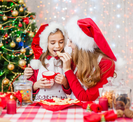 Happy family at Christmas. Mother and little girl eating christmas cookies at home. 스톡 콘텐츠