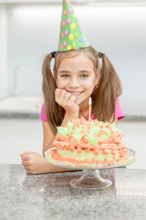 Smiling girl celebrating his birthday with cake at kitchen. Stockfoto