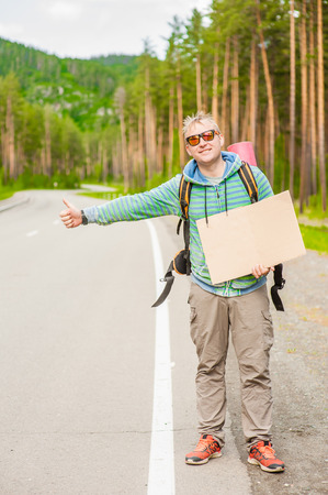man travels hitchhiking with a cardboard sign in her hands. Space for text.