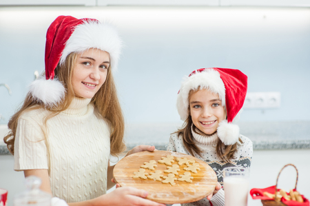 Happy mother and daughter with Christmas cookies at home.