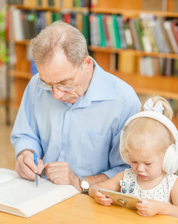 Little girl uses the application on the phone, and an elderly man reads a book in the library. Stock fotó