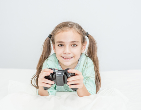 Smiling little girl playing video games at home. Empty space for text.