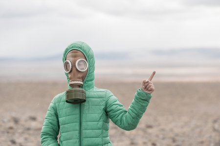 Boy in a gas mask on a deserted field pointing away on empty space. Stock Photo