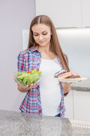young pregnant girl chooses between donut and vegetable salad. Stock Photo