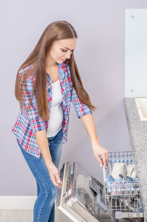 Young pregnant woman taking dishes from dishwasher in kitchen. Reklamní fotografie