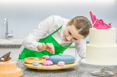 Young confectioner decorating cake at kitchen. Focused on hand.