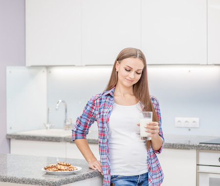 Attractive pregnant woman with milk and cookies at kitchen. 免版税图像