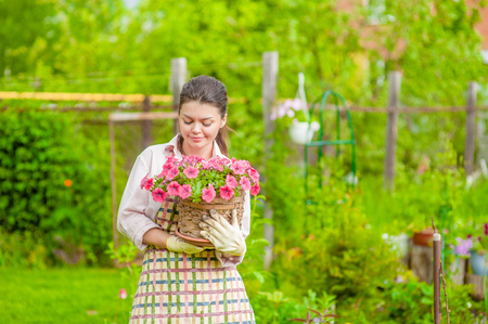 Young woman with flowers at back yard. Empty space for text.