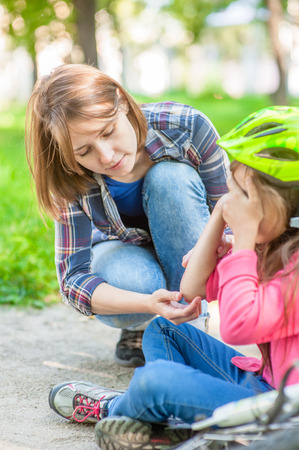 Young mom looks at the wound of his daughter, who fell from a bicycle. Фото со стока
