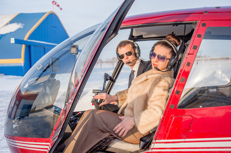 young woman and pilot in in the cockpit of a helicopter. Stockfoto