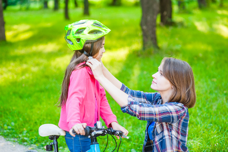 Happy family. Mother dresses her daughter's helmet at summer park.