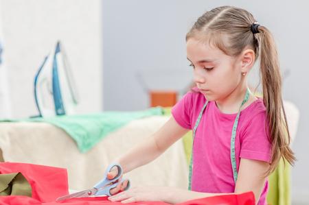 Kleines Mädchen schneidet Kleiddetail mit Schere. Platz für Text. Standard-Bild