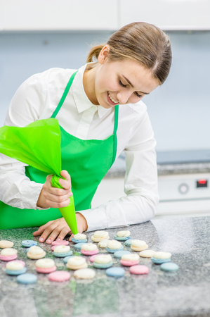 Smiling chef with confectionery bag squeezing cream filling to macarons shells.
