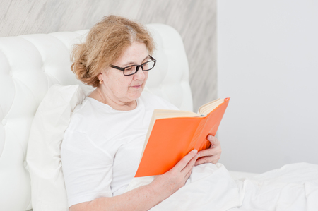 Senior woman with  book on the bed. 版權商用圖片