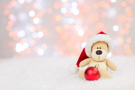 Toy bear with red santa hat and tree toy ball. Christmas holidays background with copy space for your text.