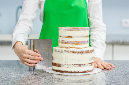 Close up pastry cook  makes a wedding cake with white cream  using a  cooking spatula  at kitchen. Фото со стока