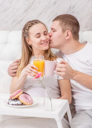 Romantic happy couple having breakfast at bedroom.