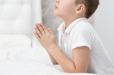 Young boy praying at home.