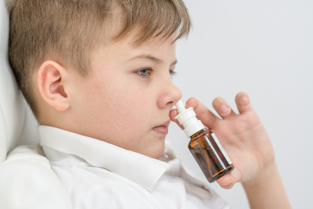 Ill boy with flu using nose spray.